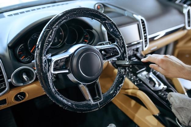 Рабочий с щеткой вытирает рулевое колесо автомобиля, химчистка и деталировка.