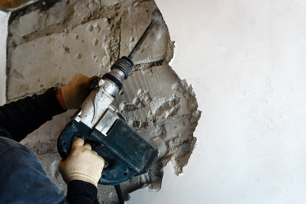 벽에서 석고를 제거하는 철거 망치로 작업자