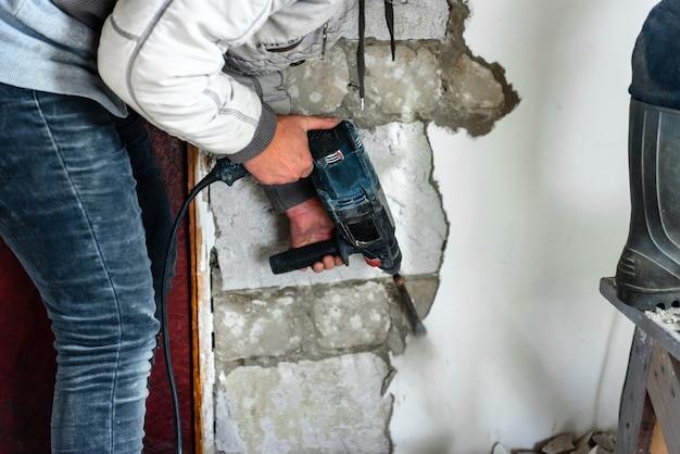 Рабочий с отбойным молотком, снимая штукатурку со стены