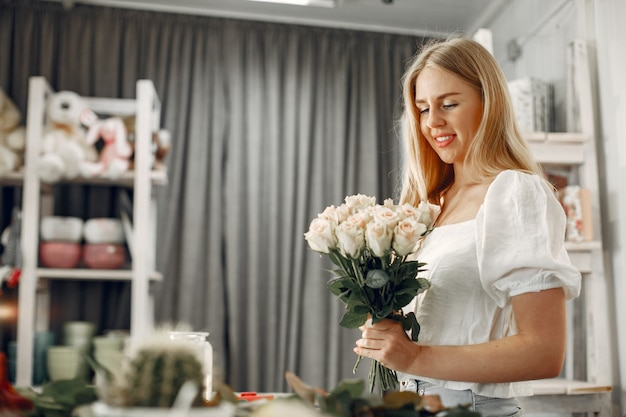 꽃과 노동자입니다. 여자는 꽃다발을 만든다. 작업하는 귀여운 여자