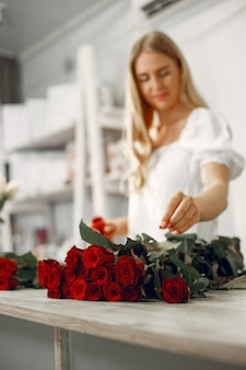 Worker with flowers. woman makes a bouquet. cute girl working