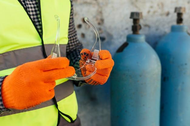 Operaio con guanti che tengono occhiali protettivi