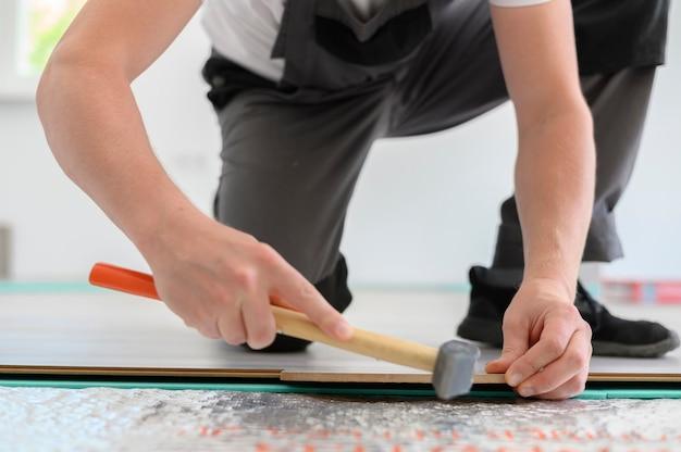 新しいラミネートフローリングの正面図の家の改装サービスをインストールするハンマーを持つ労働者