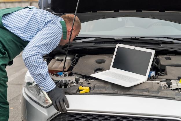 Рабочий с ноутбуком делает диагностику двигателя автомобиля