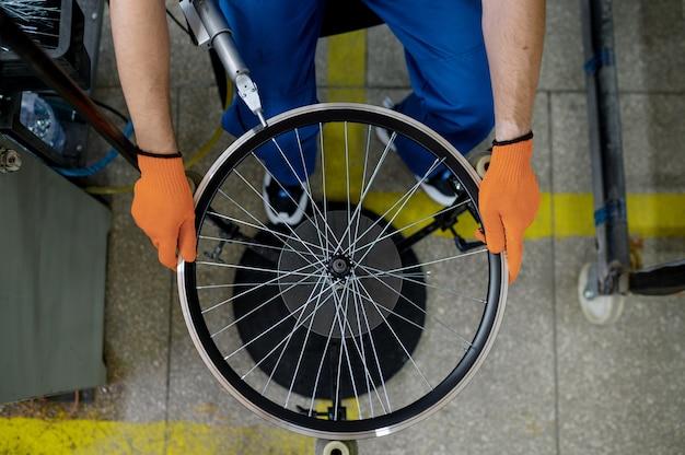 공작 기계를 가진 작업자는 공장, 평면도에 새로운 자전거 림을 설치합니다. 작업장에서 자전거 바퀴 조립, 사이클 부품 설치