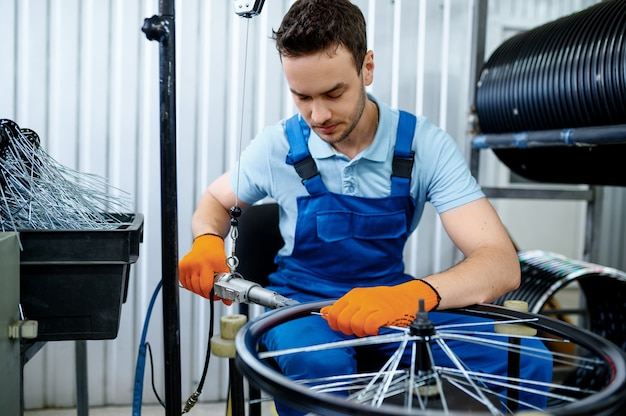공작 기계를 가진 작업자가 공장에 새 자전거 스포크를 설치합니다. 작업장에서 자전거 바퀴 조립, 사이클 부품 설치