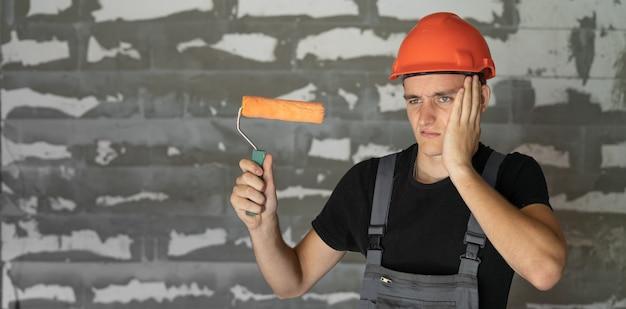 Рабочий с оранжевым шлемом у стены из камней. держат в руках ролик, хлопают себя по лицу рукой