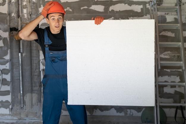 Рабочий с оранжевым шлемом у стены из камней. держит в руках большой лист пенопласта. держит голову рукой. копировать пространство