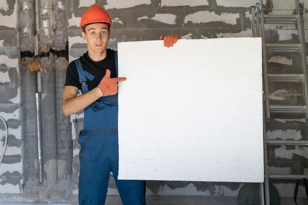 Рабочий с оранжевым шлемом у стены из камней. держит в руках большой лист пенопласта. укажите пальцем на пустое место для текста.