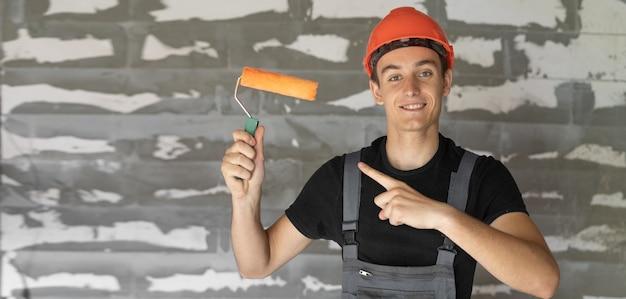 Рабочий с оранжевым шлемом у стены из камней. держит ролик в руках указательным пальцем указывает на него