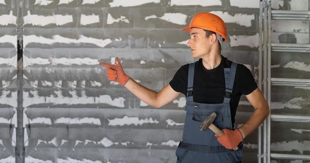 Рабочий с оранжевым шлемом у стены из камней. указывает пальцем на пустое место для текста.