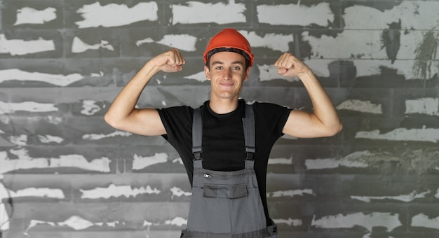 Рабочий с оранжевым шлемом у стены из камней. поднимает руки вверх показывает силу
