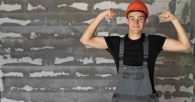 Рабочий с оранжевым шлемом у стены из камней. поднятие рук показывает силу. скопируйте пространство.