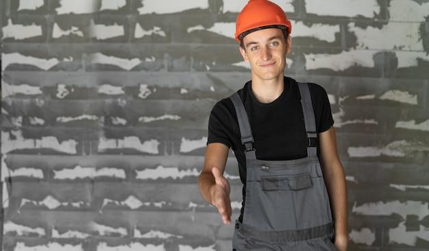 Рабочий с оранжевым шлемом у стены из камней. протягивает руку, чтобы пожать руку.