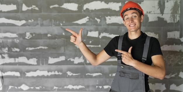 Рабочий с оранжевым шлемом у стены из камней. указательные пальцы рук указывают на пустое место для текста