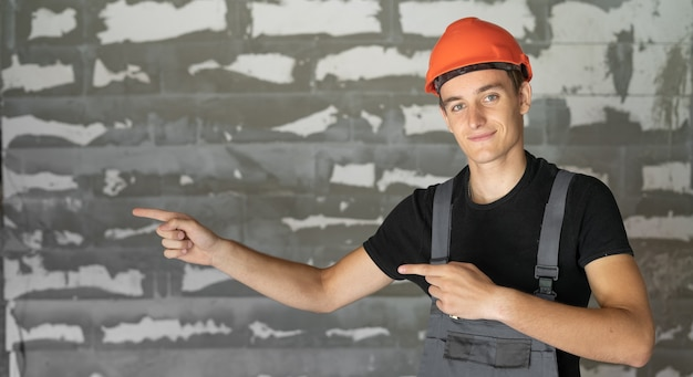 Рабочий с оранжевым шлемом у стены из камней. двумя указательными пальцами указывает на пустое место для текста.