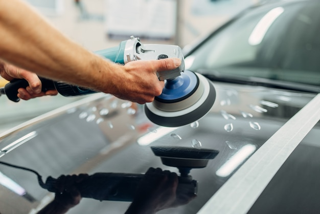 Worker with polishing machine cleans car hood. auto detailing on carwash service