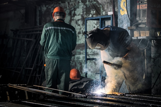 A worker with a protective mask is welding metal using a welding machine