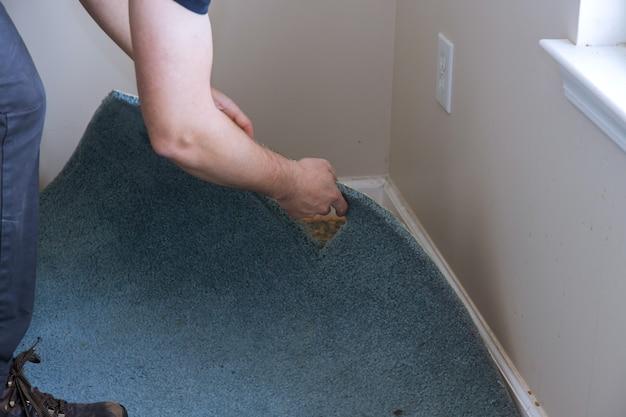 거실에서 오래된 카펫을 제거하는 작업자