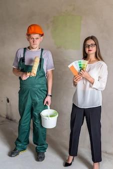 롤러 및 페인트 통 및 색상 샘플러를 가진 여자와 노동자