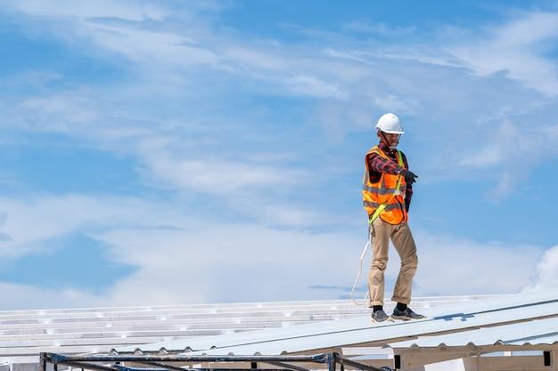 Рабочий с инструментами кровельщика в защитном снаряжении устанавливает новую крышу на верхней крыше на строительной площадке, металлическая крыша.