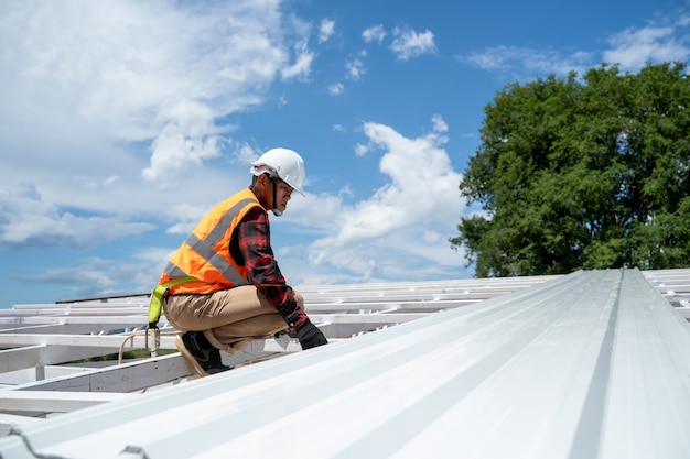 Worker with roofer tools wearing protective gear installing new roof on top roof at construction site,metal roof.