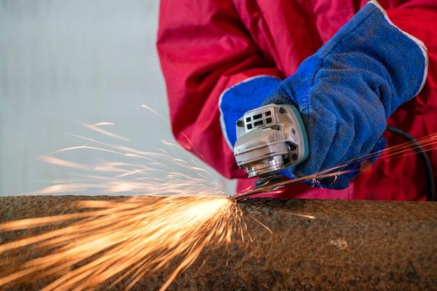 Рабочий в защитном костюме шлифует работу в строительной мастерской