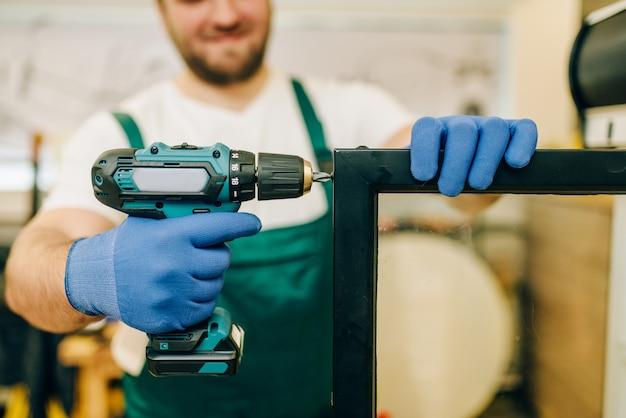 ドライバーで労働者は自宅の冷蔵庫のドアを修理します。冷蔵庫の修理、専門サービス