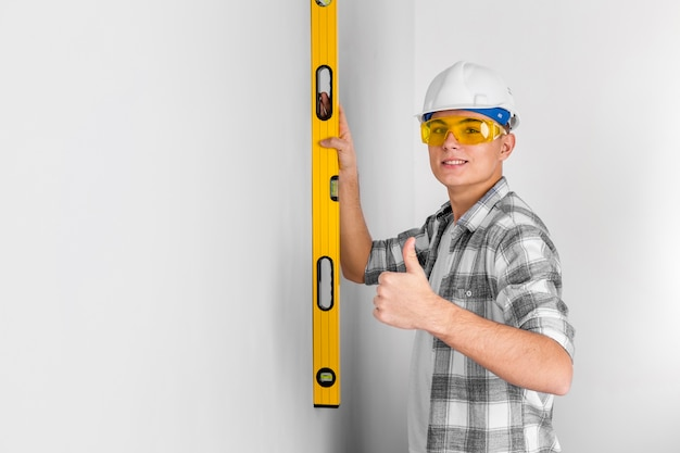 Рабочий с уровнем духа на стене