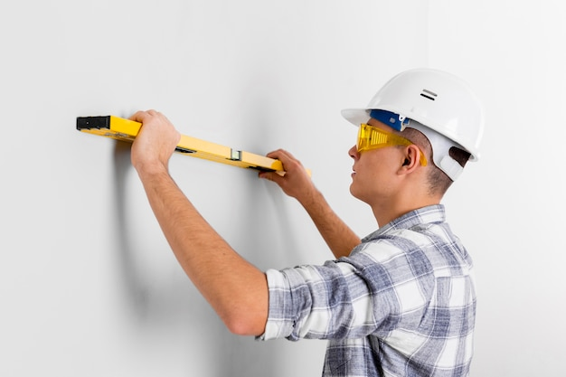 Worker with spirit level on a wall