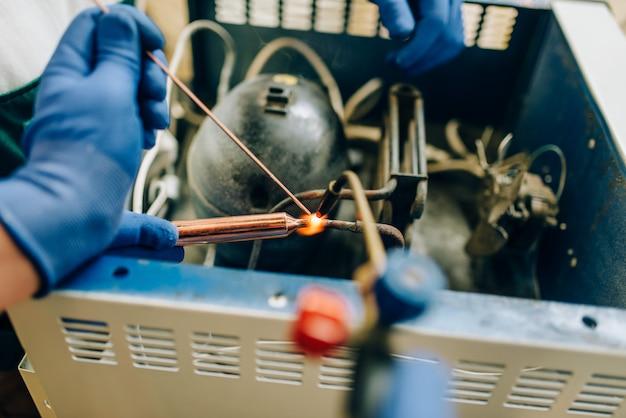 バーナーを持つ労働者は、自宅で冷蔵庫の冷却システムを修理します。