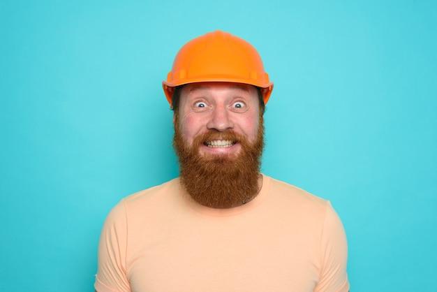 Рабочий в желтой шляпе доволен своей работой над голубым