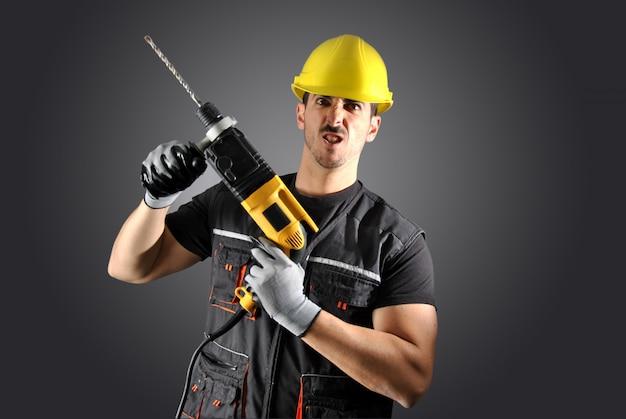 Рабочий с желтым шлемом, дрелью и молотком