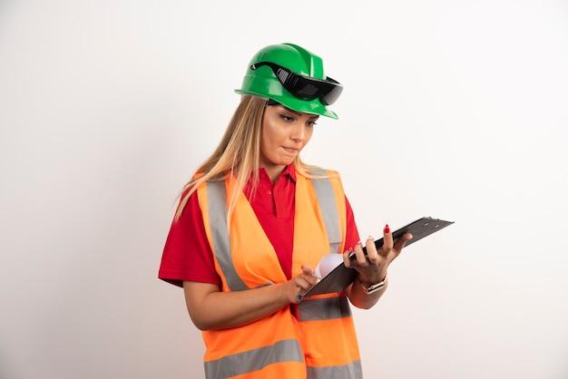Industria della donna operaia in giubbotto guardando negli appunti