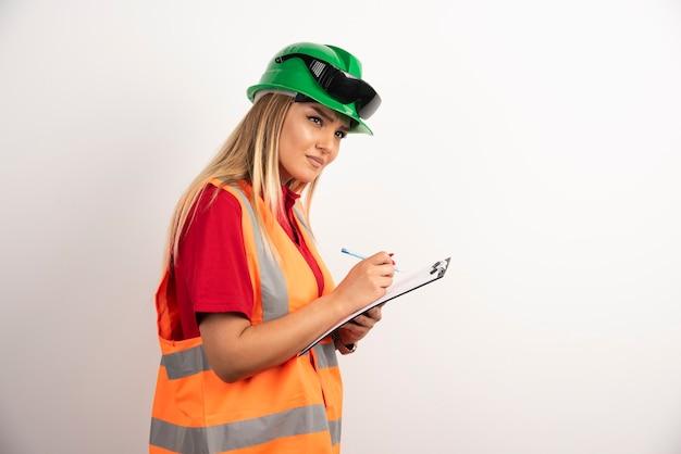 Industria della donna dell'operaio che scrive negli appunti