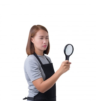 Worker woman, investigator in gray shirt and apron is holding or looking with magnifying glass