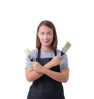Worker woman or service woman in gray shirt and apron is holding paint brush