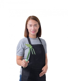 Worker woman or service woman in gray shirt and apron is holding shovel for cultivators