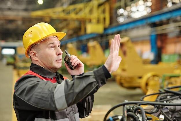 Рабочий, работающий с оборудованием на заводе