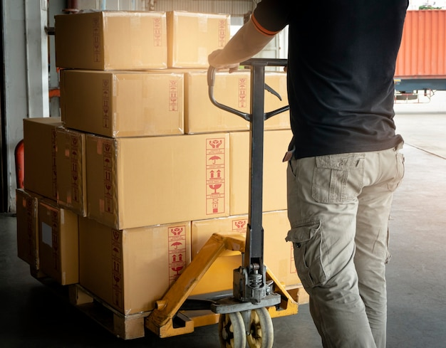 Worker working with hand pallet truck unloading cargo boxes shipment at the warehouse