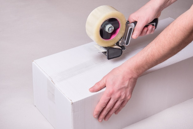Worker works with tape dispenser, closing cardboard industrial box