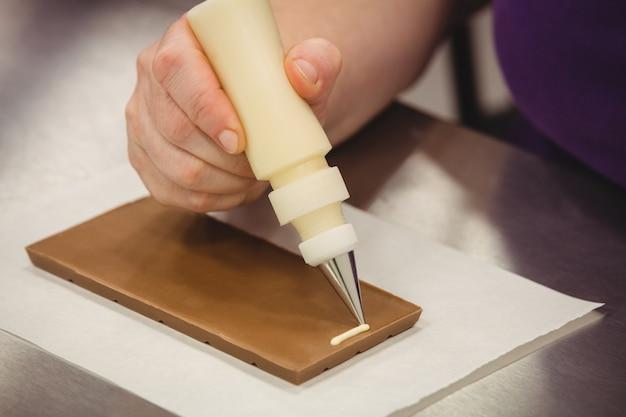 Рабочий пишет с трубкой на шоколадной табличке