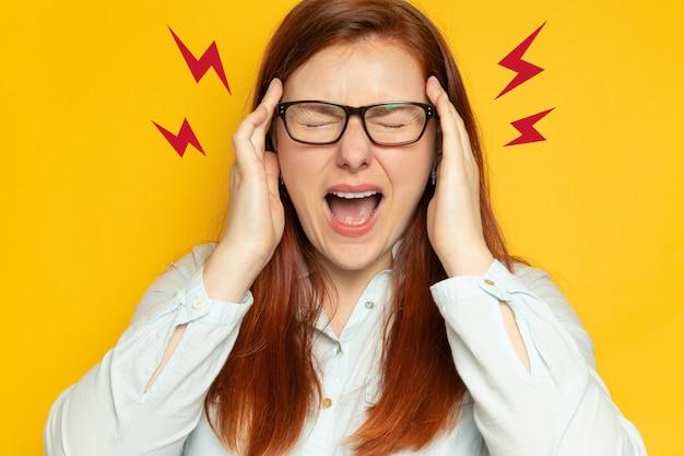 黄色の壁の壁に頭痛とシャツと視力メガネの労働者の若い女性。ストレス、疲労の人々の概念。