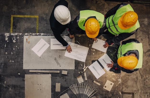 工場で文書を扱う安全ヘルメットの労働者と管理者