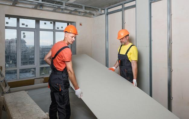 Рабочие несут гипсокартон для крепления к стене.