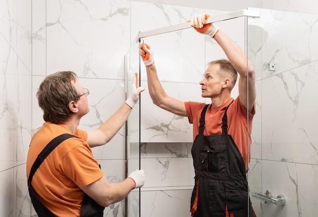 労働者はシャワーエンクロージャーのガラス壁を金属棒で接続しています。
