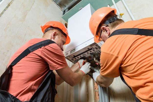 労働者はパイプをガスボイラーに接続しています。