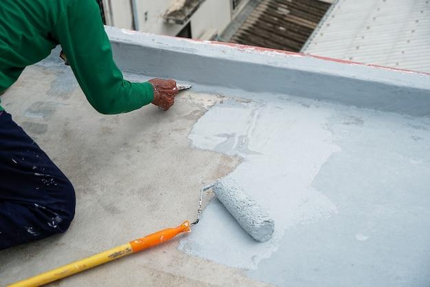Рабочие ремонтируют трещины в полу. ремонт гидроизоляционного настила пола.
