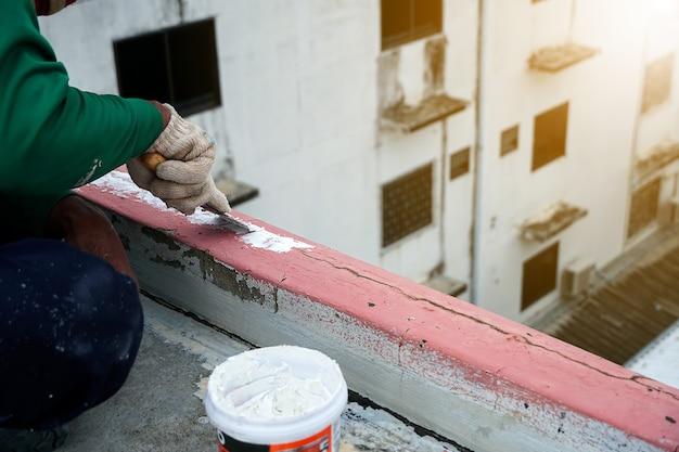 Рабочие заделывают трещины в штукатурке пола мастерком ремонт гидроизоляционного настила