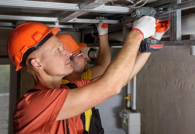 Рабочие устанавливают на потолок сложный каркас для гипсокартона.